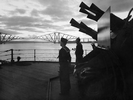 An eight-barrelled two-pounder 'pom-pom' gun on HMS RODNEY silhouetted at sunset in the Firth of Forth, October 1940.