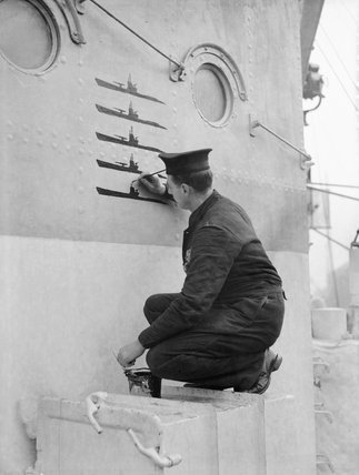 Ordinary Seaman P S Buckingham, keeping a record of U-boat kills on the side of the wheelhouse on board HMS HESPERUS, docked at Liverpool, 6 December 1943.