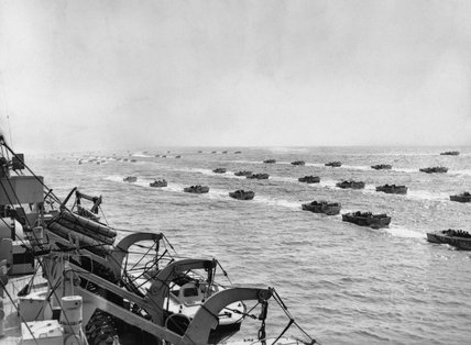 A fleet of LCAs (assault landing craft) pass a landing ship as King George VI takes the salute on board the headquarters ship HMS BULOLO off Beaulieu, 24 May 1944.
