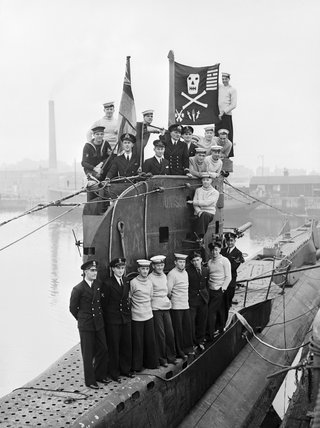 The crew of HM Submarine UNISON display their 'Jolly Roger' at Plymouth, having returned from a successful 16 months in the Mediterranean, 10 October 1943.