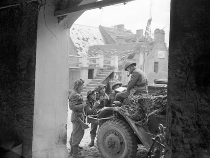 Captain J F Burgess, Royal Artillery, briefing a party of FOBs (Forward Observation Bombardment) in a Normandy village, June 1944.