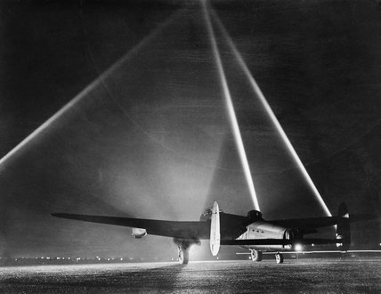 An Avro Lancaster Mk III of No. 103 Squadron pauses on the flarepath at Elsham Wolds, Lincolnshire, before taking off for a raid on Duisburg, 26 March 1943. In the background three searchlights form a cone to indicate the height of the cloud base.