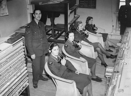 WAAF telephone operators in RAF Fighter Command's Sector 'G' Operations Room at Duxford, Cambridgeshire, receiving reports of enemy aircraft plots from Observer Corps posts, September 1940.