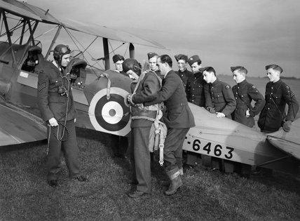 An Air Training Corps cadet secures his parachute, before an air experience flight in a de Havilland Tiger Moth at Biggin Hill, Kent, 4 January 1942.