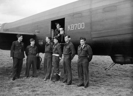 The crew of the first Canadian-built Avro Lancaster X to arrive in Britain, christened the 'Ruhr Express', photographed with their mascot at Northolt, Middlesex, on 15 September 1943.