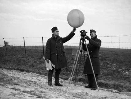 Two corporals of an RAF mobile meteorological unit prepare to send up a balloon to measure the wind speed and cloud height, 2 January 1940.