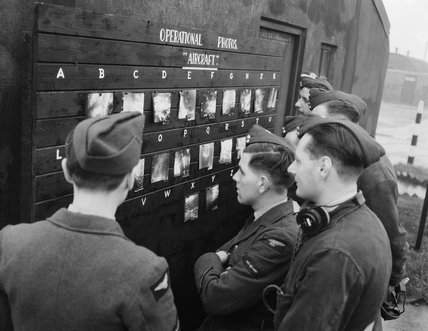 RAF personnel on a bomber station in Britain view a display of target photographs taken by their aircraft during the previous night's operation over Germany, 1943.