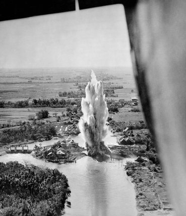 Photograph taken from a Consolidated Liberator B Mark VI of No. 356 Squadron showing a bomb exploding on lock gates on the Khlong Phasi Charoen canal near Bangkok in Thailand, 18 April 1945.