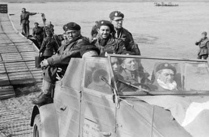 Airborne troops cross back over the Rhine in a captured German Kubelwagen car, March 1945.