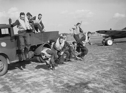 Pilots of No. 19 Squadron RAF stage a mock 'scramble' from the back of a truck at Fowlmere near Duxford, September 1940.
