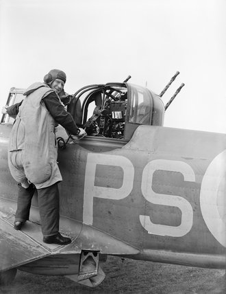 An air gunner of No. 264 Squadron RAF about to enter the gun turret of his Boulton Paul Defiant Mk I at at Kirton-in-Lindsey, Lincolnshire, August 1940.