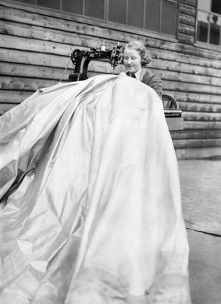 A member of the WAAF (Women's Auxiliary Air Force) machine-stitching a patch onto a kite balloon at an RAF station, May 1940.