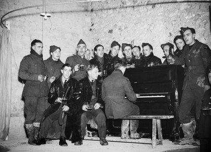 RAF personnel enjoy a 'sing song' round the piano in a billet somewhere in France, 19th December 1939.