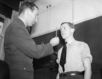 A medical officer conducts an eye test during medical examinations of aircrew candidates in London, May 1940.