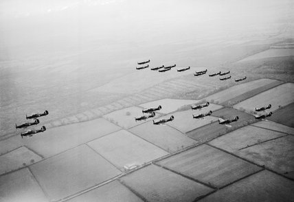 Hawker Hurricanes of No 1 Squadron, Royal Air Force, based at Wittering, Cambridgeshire, followed by a similar formation of Supermarine Spitfires of No 266 Squadron, during a flying display for aircraft factory workers, October 1940.