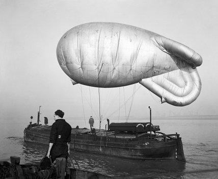 A kite balloon tethered to the balloon barge NORMAN WADE on the River Humber, at No. 17 Balloon Centre at Sutton-on-Hull in Yorkshire, January 1943.