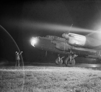 An Avro Lancaster Mk III of No. 49 Squadron RAF is guided to its dispersal point at Fiskerton, Lincolnshire, after returning from a raid on Berlin, 22 November 1943.