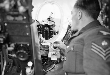 A ground crew sergeant demonstrates the operation of the photo-reconnaissance camera in a de Havilland Mosquito of No. 540 Squadron RAF at Benson, Oxfordshire, August 1943.