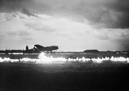 FIDO (Fog Investigation Dispersal Operations) petrol burners are ignited on either side of the main runway at Graveley, Huntingdonshire, as an Avro Lancaster of No. 35 Squadron RAF takes off in deteriorating weather, 28 May 1945.