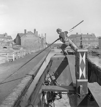 Miss March pushes her narrowboat the 'HEATHER BELL' off from the canal bank during a journey carrying flour from Worcester to Tipton during 1942.