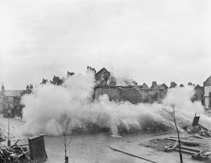 A bomb damaged house is brought down with high explosives to reproduce the destruction of a building by bombing during tests on the Morrison indoor shelter in 1941.