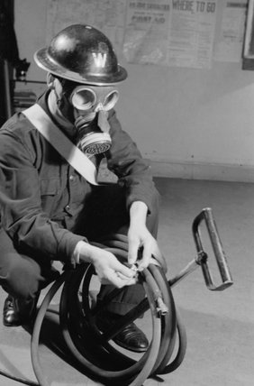 An ARP Warden wearing a gas mask tidies the hose of his stirrup pump at an ARP post in Britain during the Second World War.
