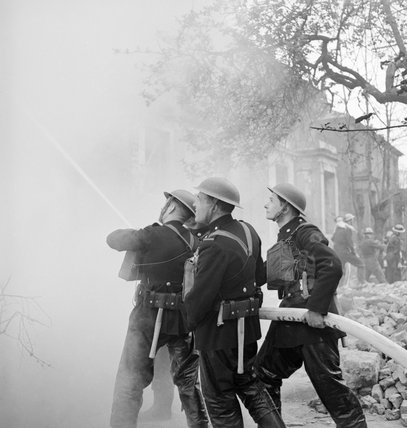 Members of the National Fire Service tackle a blaze in a house during a Civil Defence exercise in Fulham, London in 1942.