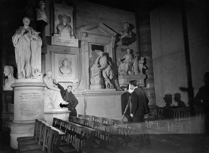 Director Humphrey Jennings stretches to touch a piece of sculpture in Poets' Corner in Westminster Abbey, as he suggests a shot for camera operator Chick Fowle of the Crown Film Unit in January 1941.