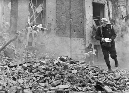 An Air Raid Warden runs across a large pile of rubble during Civil Defence training in Fulham during 1942.