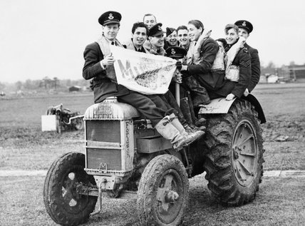 Pilots of No. 601 Squadron RAF use a tractor to negotiate muddy conditions on their airfield at Exeter, November 1940.