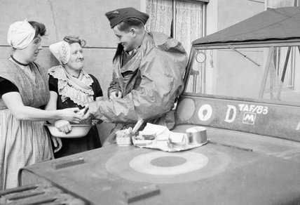 An RAF sergeant shares an alfresco lunch with two Dutch women at Nieuland, near Middelburg, soon after the town had been liberated by Allied forces, November 1944.