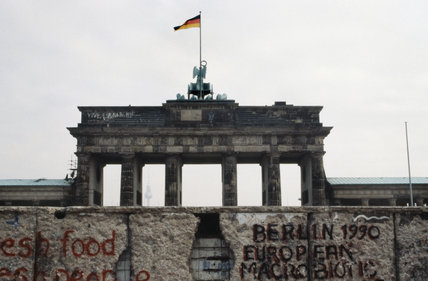 The West German flag flies over the Brandenburg Gate in Berlin, with a graffiti covered section of the Berlin Wall in the foreground, 1990.