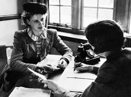 Iris Joyce talks with a recruiting officer as she enrols in the Women's Land Army during 1942.