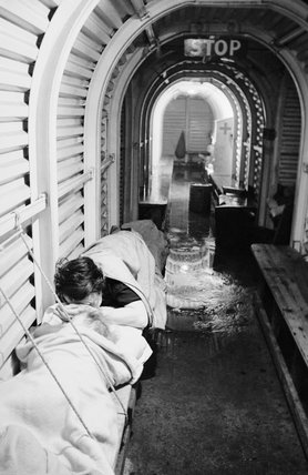 A mother and child sleep in a trench shelter in London during November 1940.