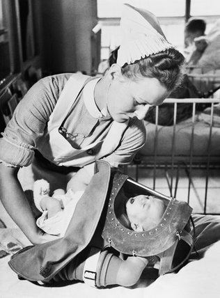 A nurse places a crying baby into its gas respirator during a drill at a London hospital in 1940.