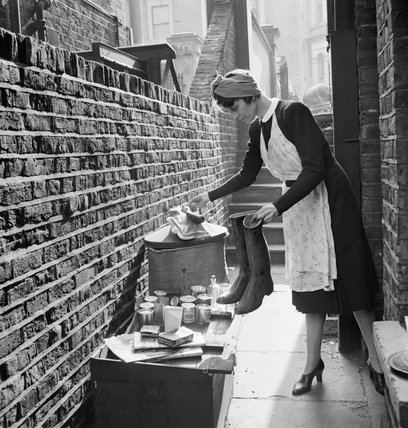 A British housewife puts out items for salvage during 1942.