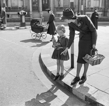 A mother teaches her daughter to cross the road in safety during 1942.