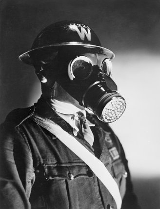 An Air Raid Warden wearing his steel helmet and duty gas mask during the Second World War.
