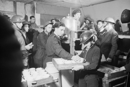 Tea and buns are supplied by local Air Raid Precautions (ARP) workers to fellow ARP workers and civilians in this basement shelter in South East London during 1940.