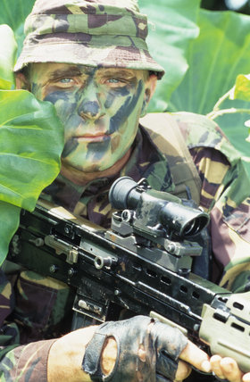 Portrait of a camouflaged British soldier crouching in dense foliage in Belize, June 1993.
