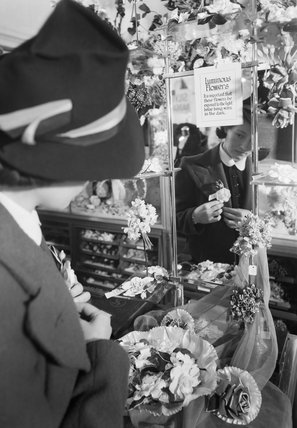 A woman pins a luminous flower to her jacket lapel in Selfridge's department store, London. These flowers were one of numerous blackout accessories available in 1940 to make pedestrians more visible on the dark streets of the capital.