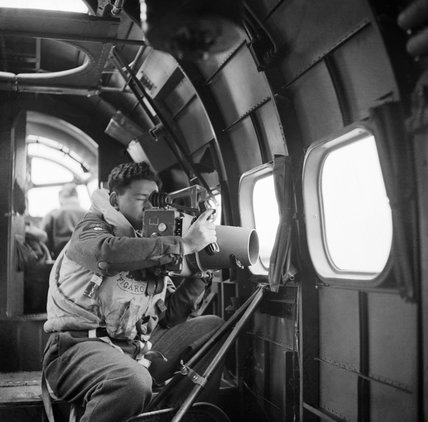A crewman on board an RAF Coastal Command Lockheed Hudson of No. 269 Squadron, using an F.24 camera during an ice patrol from Kaldadarnes in Iceland, 5 May 1942.