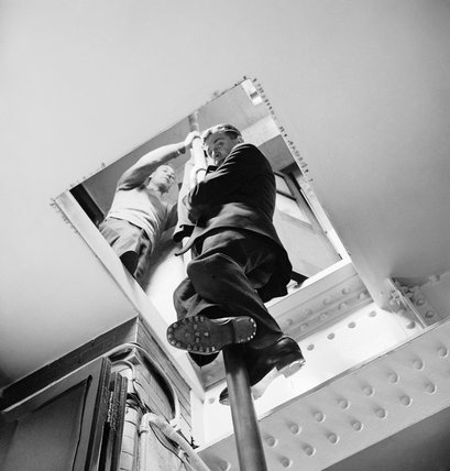 A fireman of the National Fire Service slides down the fireman's pole at Fulham Fire Station during a large-scale Civil Defence training exercise in 1942.