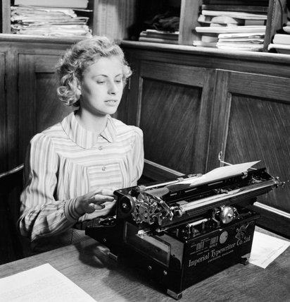 Iris Joyce at work on her typewriter in an office prior to joining the Women's Land Army in 1942.