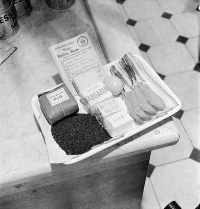 Tray containing a ration book and the weekly ration of sugar, tea, margarine, 'national butter', lard, eggs, bacon and cheese as issued to an adult in Britain during 1942.