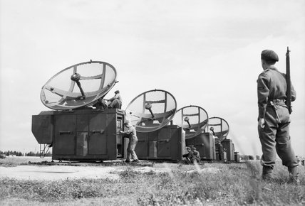 A Royal Air Force Regiment sentry stands guard whilst German technicians assemble captured Mannheim radar equipment at Grove airfield in Denmark in preparation for sending it to the UK for evaluation, 2 August 1945.
