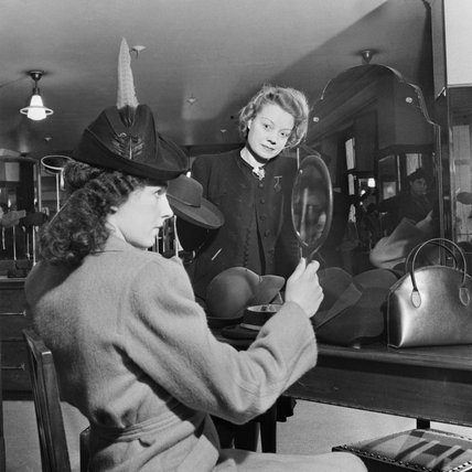 A customer tries on a new hat in the millinery department of Bourne and Hollingsworth on London's Oxford Street in 1942.