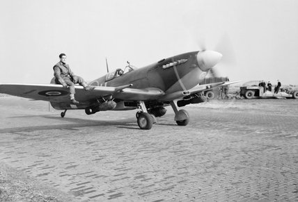 A Supermarine Spitfire Mk IXE of No. 412 Squadron RCAF, armed with a 250-lb GP bomb under each wing, taxies out for a sortie at Volkel, Holland, 27 October 1944.