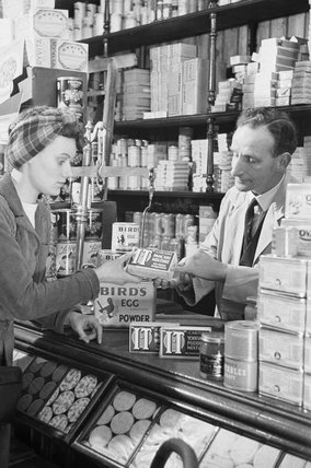 Customer making a purchase in a grocery shop during the Second World War.