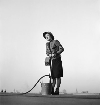 A female Fire Guard using a stirrup pump on the roof of a building in London, 1941.